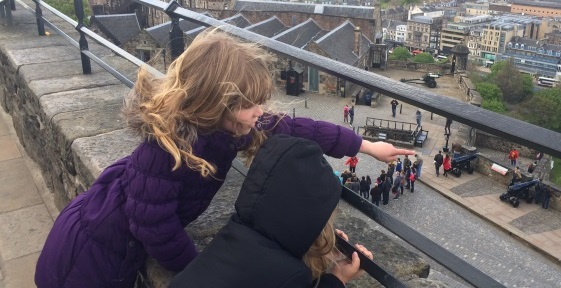 Two children at Edinburgh Castle pointing down at the city of Edinburgh