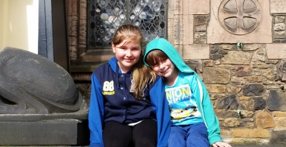 Two girls sitting in front of Edinburgh Castle