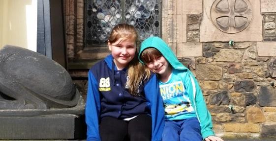 Two girls sitting in front of Edinburgh Castle