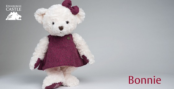 A photograph of a white bear toy wearing a dark red dress and a dark red bow.