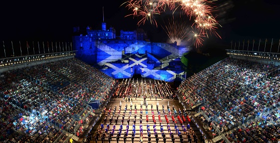 The tattoo celebrations at night in front of Edinburgh Castle lit up in the Scottish colours