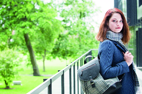 woman with red hair holds tweed backpack and wears tweed scarf as she looks at the camera