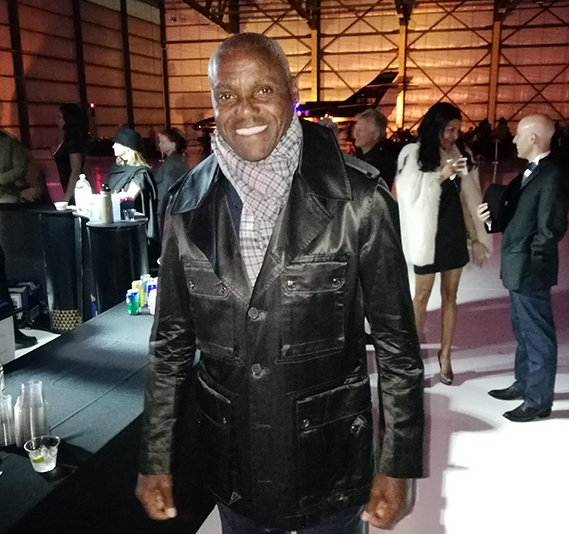 man in leather coat and tweed scarf smiles at the camera