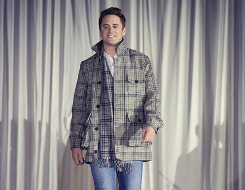 man walks towards camera wearing tweed coat