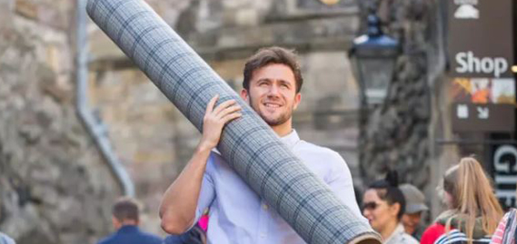 man carrying a role of tweed fabric