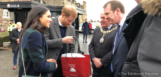 Prince Harry and Meghan Markle visiting Edinburgh Castle. Harry is holidng and Edinburgh Castle gift bag containing a gift for the happy couple