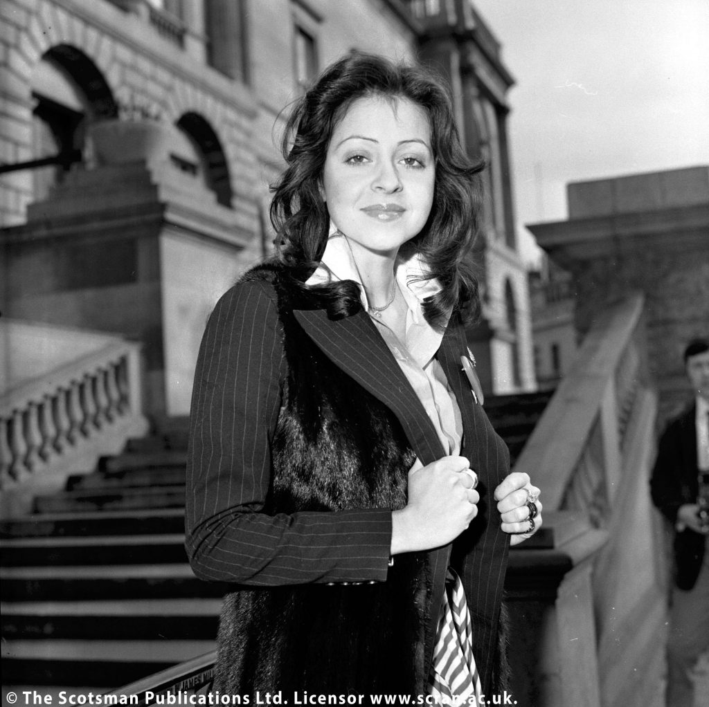 Vicky Leandros poses for a press shot in Edinburgh. She has long black hair and wears a black jacket and white shirt. The jacket features a pinstripe design.