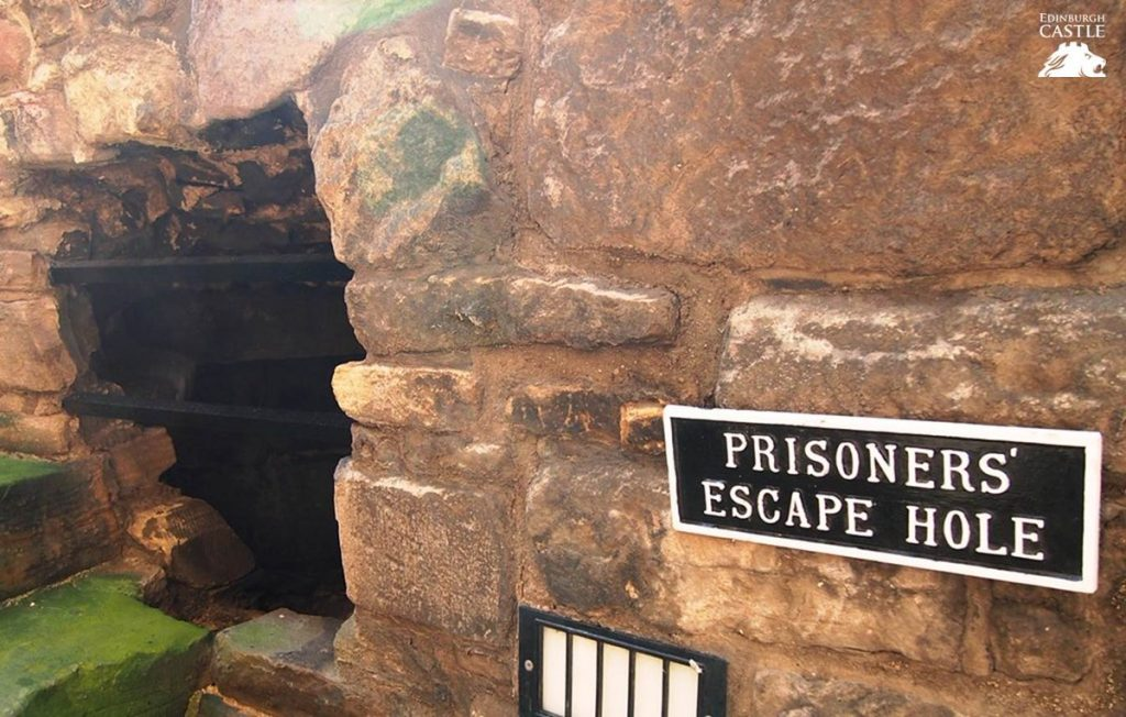 "A hole in a ancient brick wall. A black and white sign beside the hole reads ""Prisoners' Escape Hole."""