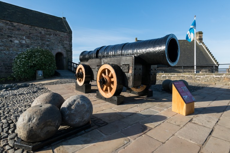 A large and ancient black cannon resting on a wooden frame with wooden and metal wheels. Three cannon balls have been placed nearby and a Scottish saltire flies from a white flag pole in the background.