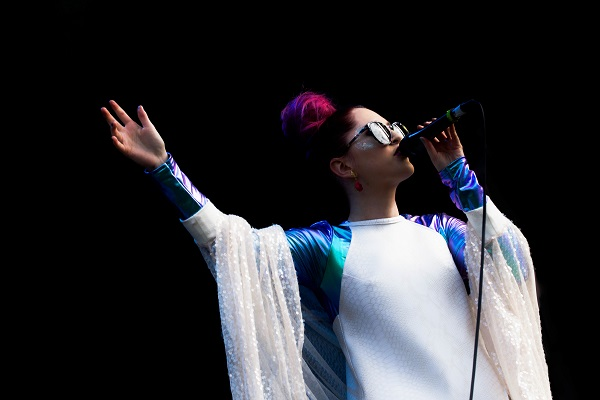 An photo of Be Charlotte. She is wearing a white and purple outfit with sunglasses. She is singing into a microphone and holding her arm aloft.