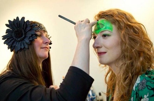 A lady wearing a black fascinator in her hair applies face make-up to another lady. Image credit Ruth Armstrong