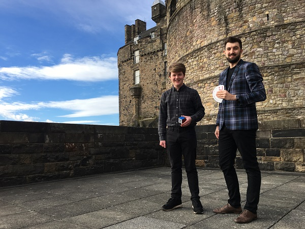 Two magicians pose outside Edinburgh Castle. Both are wearing tartan shirts. One holds a rubix cube and the other a deck of playing cards.
