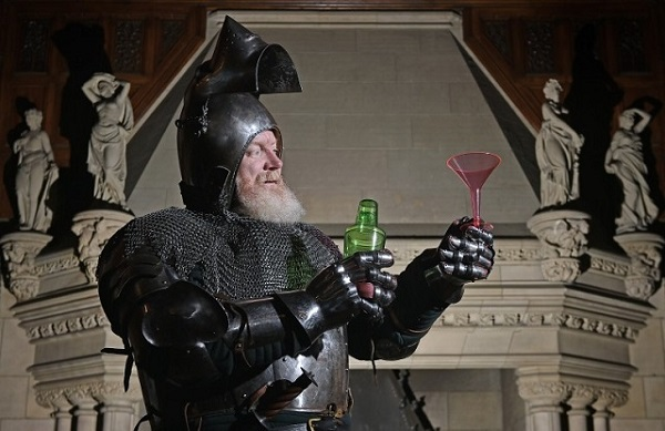 A bearded man dressed in armour and chain-mail prepares a cocktail. In his left hand he is holding a green bottle and in his right hand he is holding a pink cocktail glass. He is standing in front of an ornate stone fireplace.