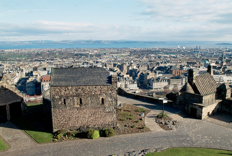 A small chapel located within the grounds of Edinburgh Castle. The city of Edinburgh and the Firth of Forth are in the background.