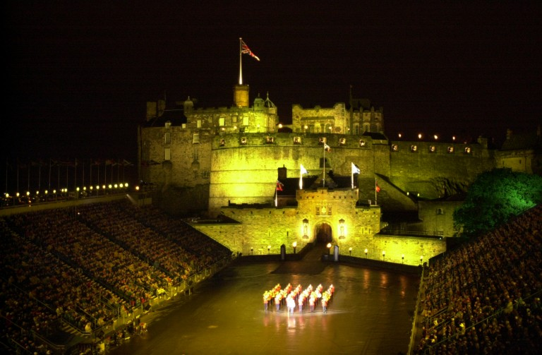 A scene from the Royal Edinburgh Military Tattoo. A military band is performing on the Castle Esplanade which is flanked by seated spectators. The Castle is floodlit in the background.