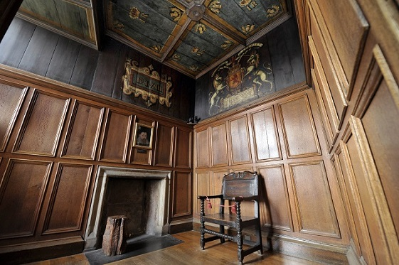 A wood paneled room with a painted ceiling