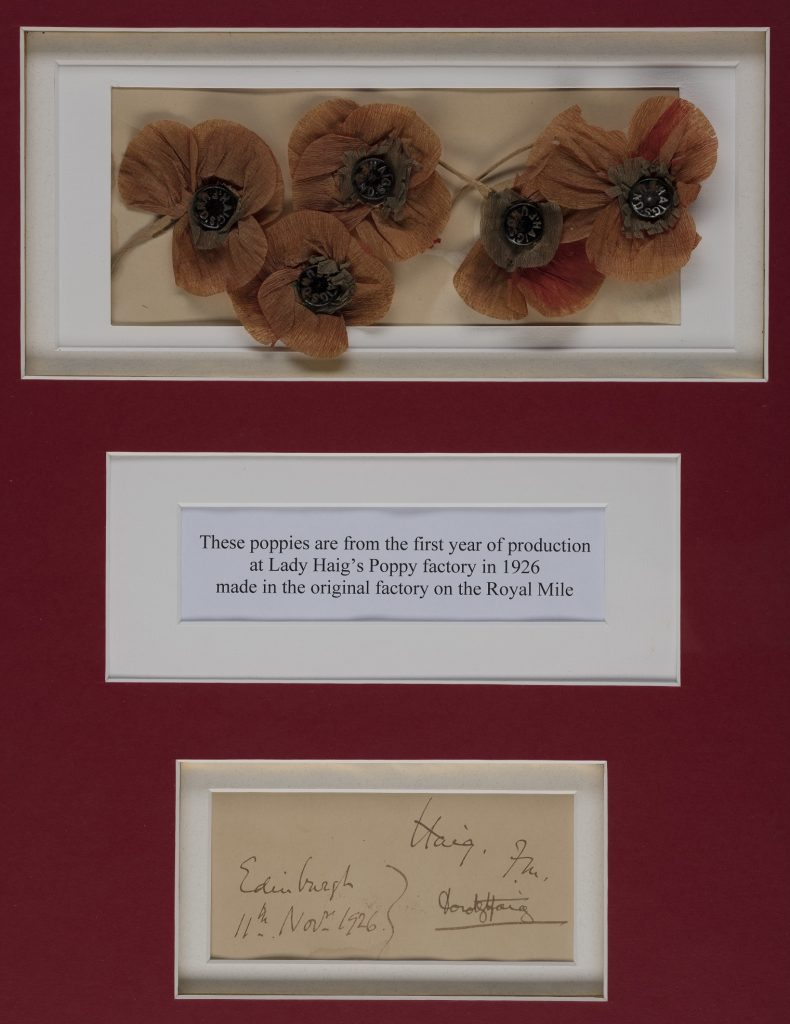 Framed remembrance poppies. The colour is a faded compared to modern day remembrance poppies and the appear to be made from tissue paper