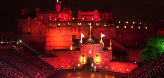 Edinburgh Castle lit in red and seating stands on esplanade