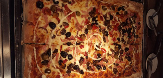 Large rectangular roast pepper and bacon pizza under a warming light