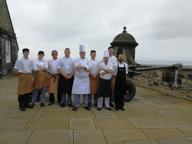 A team of chefs posing on the ramparts of Edinburgh castle