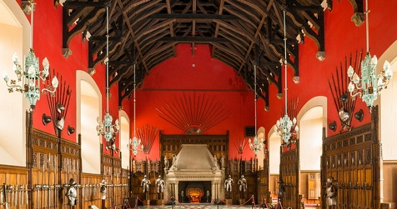 The Great Hall at Edinburgh Castle. The walls are red with a high timbered ceiling. Weapons and armour hang on the walls and a grand stone fireplace is at the end of the room.