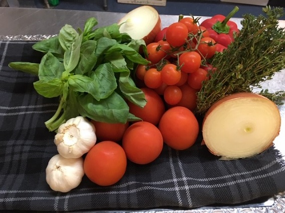 fresh ingredients for soup pictured on a table. Including onion, tomatoes, garlic and basil