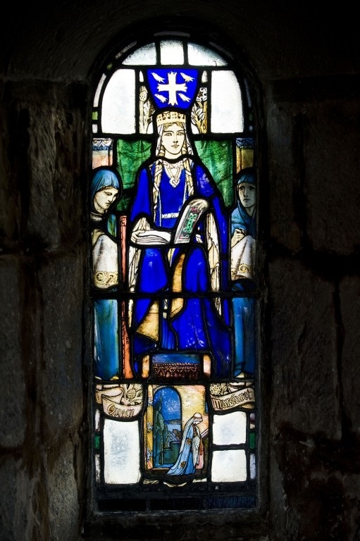 A stained glass depiction of St Margaret wearing blue robes and gold crown. An open book, perhaps a Bible, is on her lap.