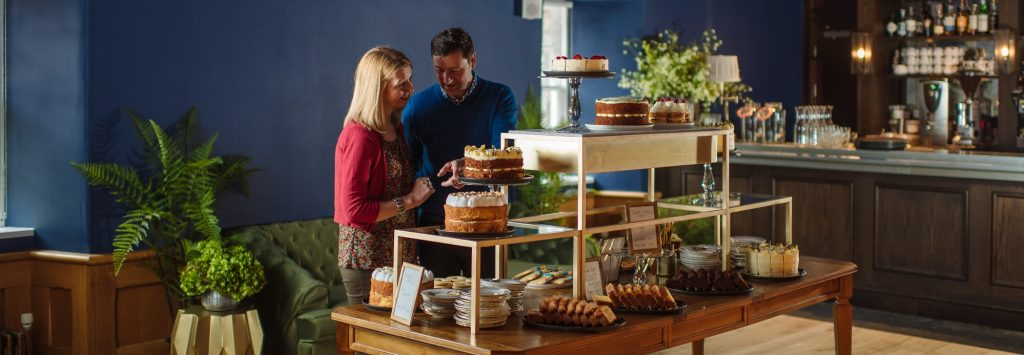 A man and a women browse a table laden with cakes and other treats