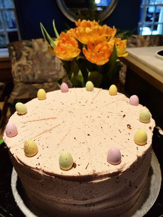 A cake with yellow icing and chocolate egg decoration