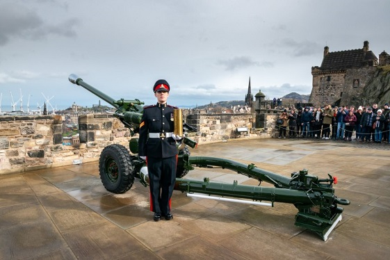 A woman in uniform stands to attention in front of a field gun. THe Edinburgh skyline is behind her