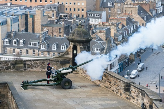 A field gun being fired from the Mills Mount Battery at Edinburgh Castle with a view of Edinburgh and the Forth in the background