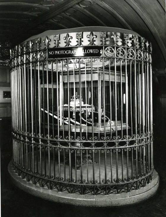 Archive image of the Crown Jewels. It is difficult to see the objects because cast iron railings obscure the view.
