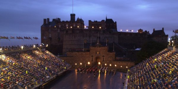 View of the Castle Esplanade by night with a military band marking in formation lit up by coloured lights