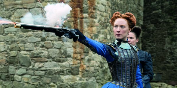 Saoirse Ronan as Mary Queen of Scots in the 2019 cinema production. She is wearing blue period costume and is firing a pistol.