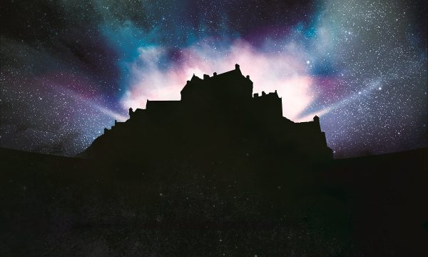 Silhouette of Edinburgh Castle with dramatic lighting emitting from within