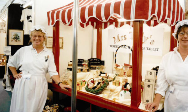 Two women in aprons and mop caps stand in front of a small market stall laden with sweet treats