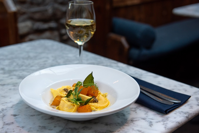 Vegan butternut squash tortellini served alongside a glass of white wine
