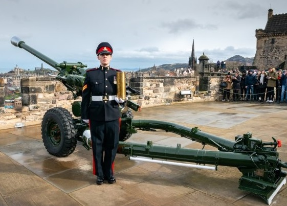 A soldier in uniform stands beside a field gun holding an artillery shell.
