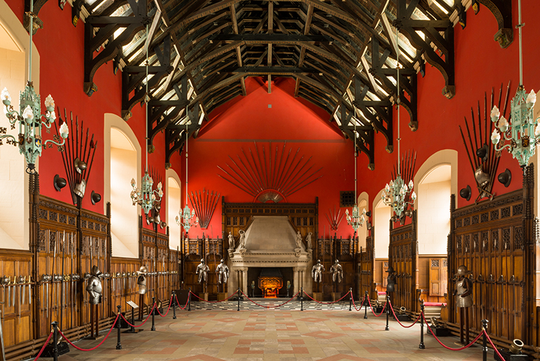 Great Hall at Edinburgh Castle. A large fireplace dominates one end of the hall. The walls are painted red on top with wood panelling on the lower half. Weapons and suits of armour line the walls