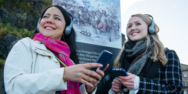 Two young women wearing headphones holding audio guide handsets