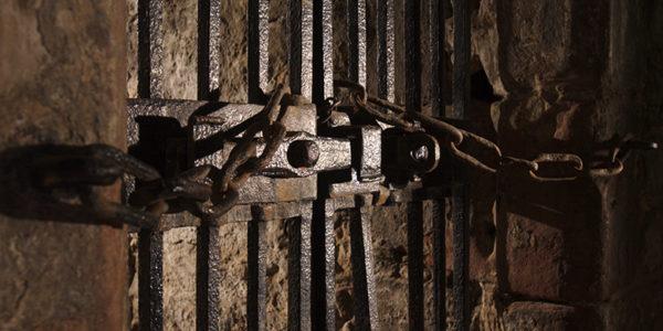 A heavy door, featuring heavy iron bars and locks.