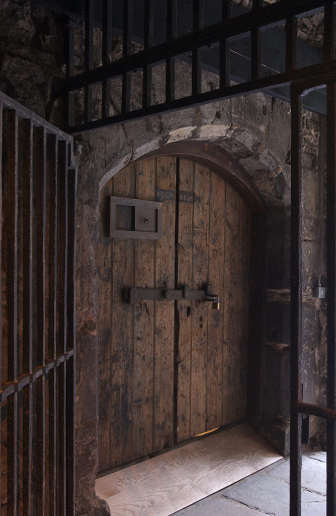 Heavy wooden doors viewed through a heavy metal barred gate.