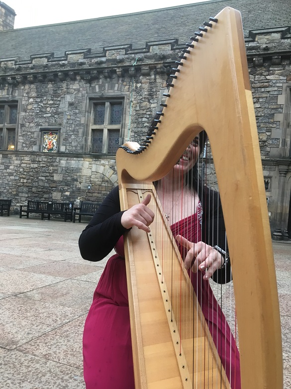 Toni playing the clarsach in a courtyard at Edinburgh Castle