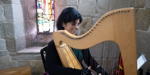A lady playing a clarsach in fornt of a stained glass window inside Edinburgh Castle