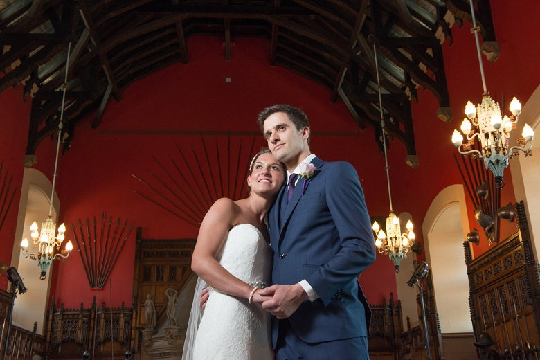 A couple pose for a wedding shoot under the timber roof of the Great hall in Edinburgh Castle