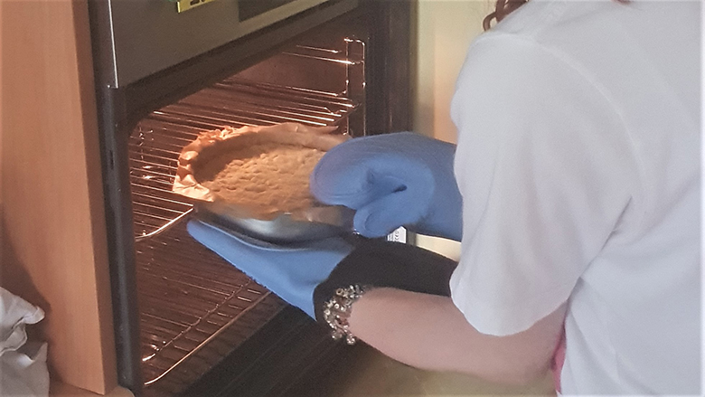 Girl wearing oven gloves removes a round tin of shortbread from the oven.