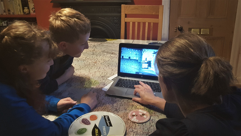 A woman and two children look at a laptop with a 3D model of Edinburgh Castle on its screen. Learning at home.