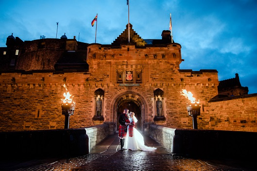 A couple pose for a wedding photo at the floodlit gates of Edinburgh Castle