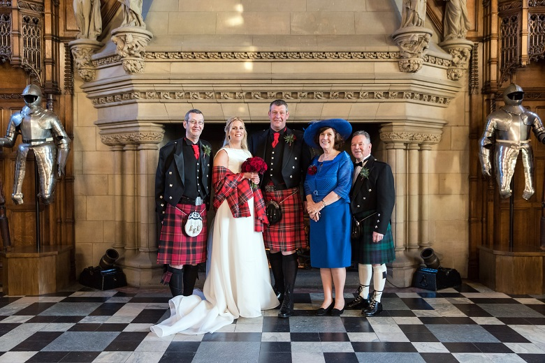 A wedding party pose for a photo in front of a large stone fireplace inside Edinburgh Castle