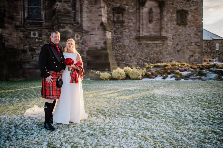 A woman in a wedding dress and a man in a kilt pose for a photo in the grounds of Edinburgh Castle. There is an attractive layer of frost on the grass.